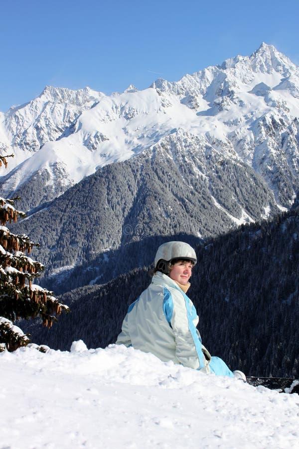Ung snowboarder i bergen royaltyfria foton