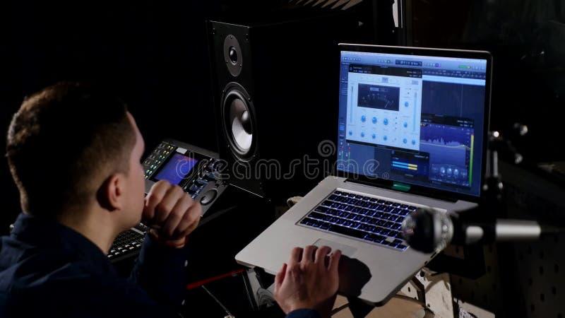 ung solid tekniker 4K i inspelningstudio genom att använda bärbara datorn på det blandande skrivbordet royaltyfria foton