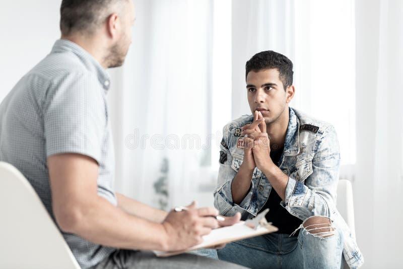 Ung spansk man som talar till en psykolog om hans framtida plommoner royaltyfri fotografi