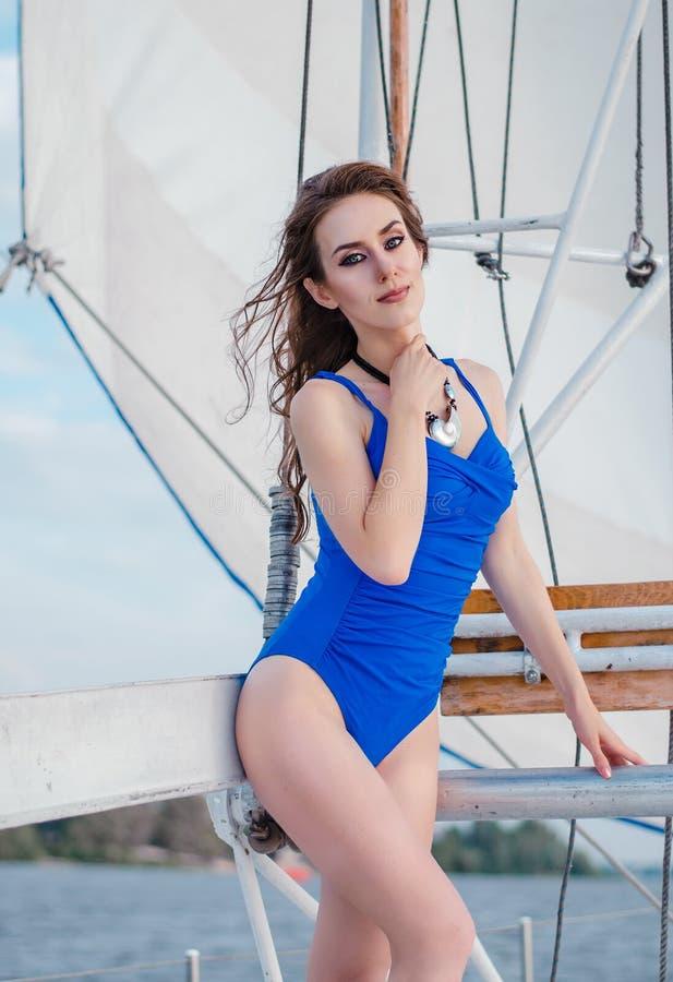 Ung spenslig kvinna i en blå stängd kryssning l för baddräktyachthav arkivfoto