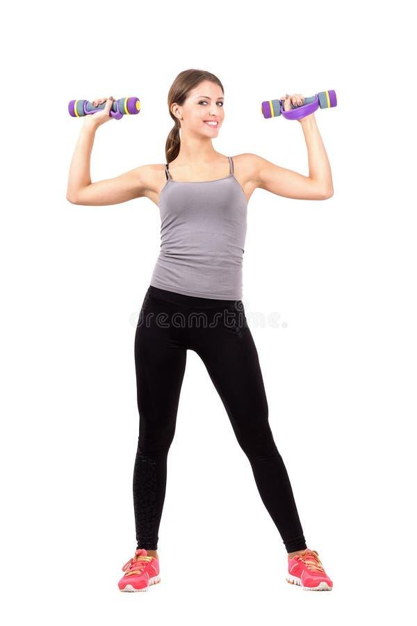 Ung sportig blond kvinna som övar med aerobiska skumhantlar arkivbild