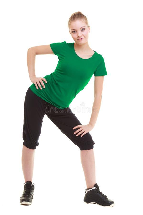 Ung sportig flicka som gör sträcka den isolerade övningen arkivfoto