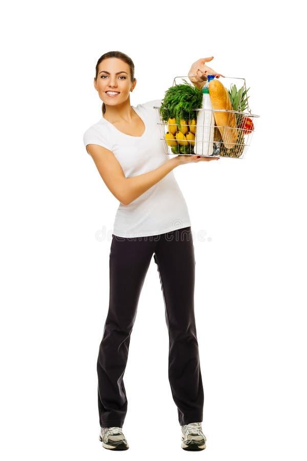 Ung sportig korg för brunettflickainnehav av mat, ny frukt och grönsaker Oavkortad tillväxt På vitbakgrund royaltyfri fotografi