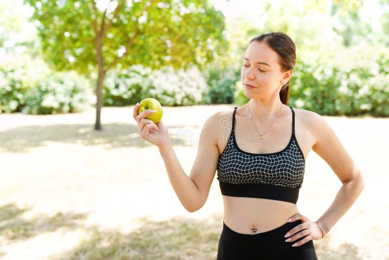 Ung sportig kvinna med det gröna äpplet, utomhus, med kopieringsutrymme royaltyfri fotografi