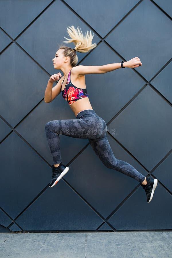 Ung sportig kvinna med passformkroppbanhoppning och spring mot svart bakgrund Kvinnlig modell i sportswearen som utomhus övar royaltyfria foton