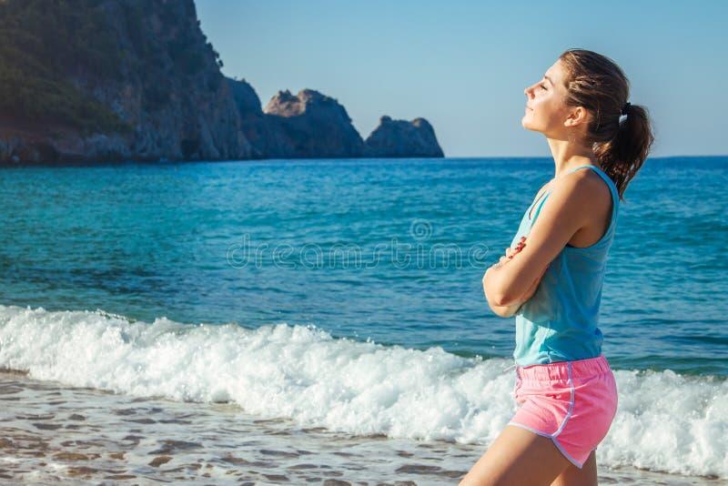 Ung sportig kvinna som har en vila efter en genomkörare på stranden arkivfoton