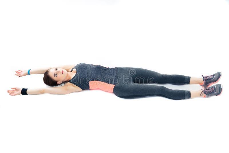 Ung sportig kvinna som ligger på golvet och sträckningen arkivfoto