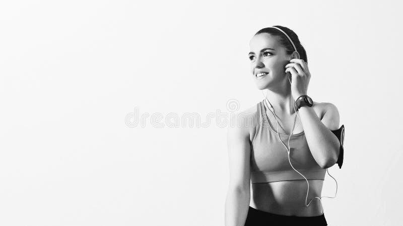 Ung sportig kvinna som lyssnar till musik med hörlurar på den smarta telefonen app för konditionmotivation Den härliga flickan i  royaltyfria bilder