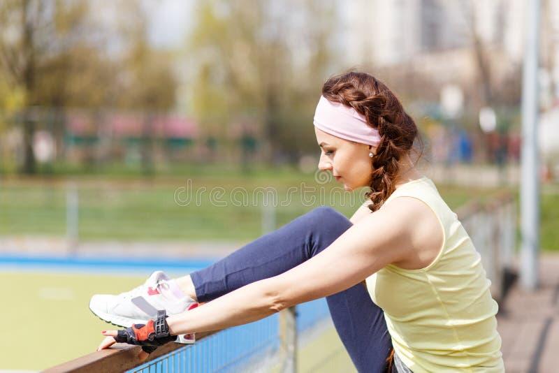 Ung sportig kvinna som sträcker, innan att jogga royaltyfria foton
