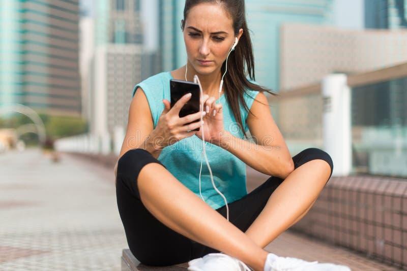 Ung sportig kvinna som vilar, når att ha övat genom att använda hennes smartphone och lyssna till musik i hörlurar Idrottsman nen royaltyfri bild