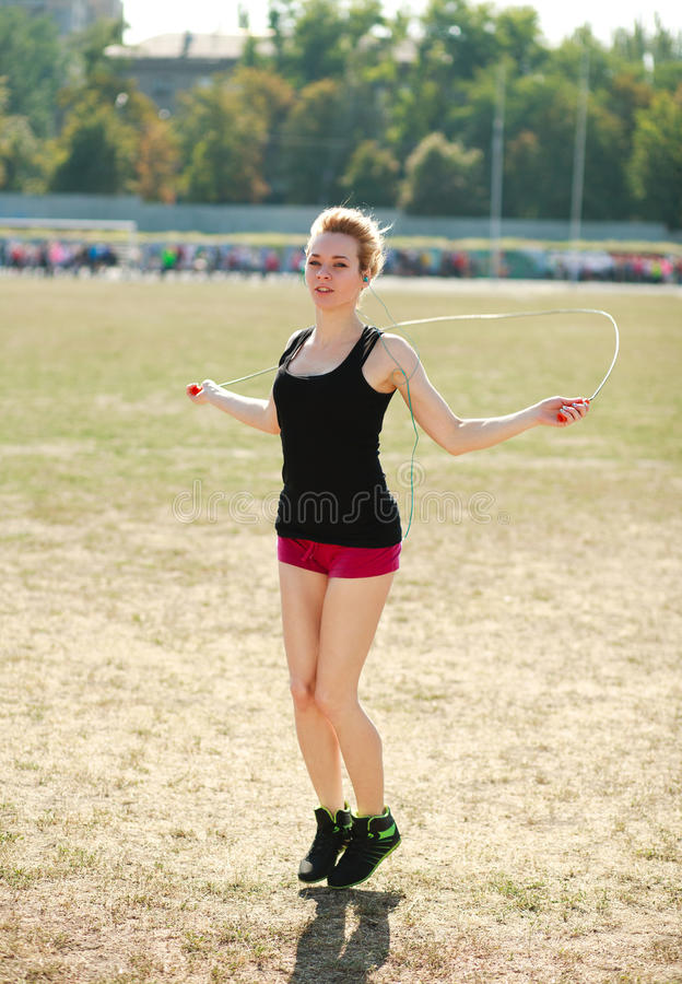 Ung sportig kvinnagenomkörare som hoppar över rep royaltyfri foto