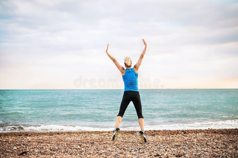 Ung sportig kvinnalöpare i blå sportswearbanhoppning på stranden utanför arkivbild