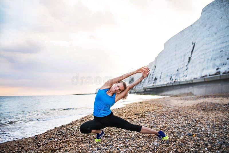 Ung sportig kvinnalöpare i den blåa sportswearen som utanför sträcker på stranden royaltyfri foto