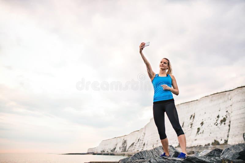 Ung sportig kvinnalöpare med hörlurar och smartphonen på stranden som tar selfie fotografering för bildbyråer