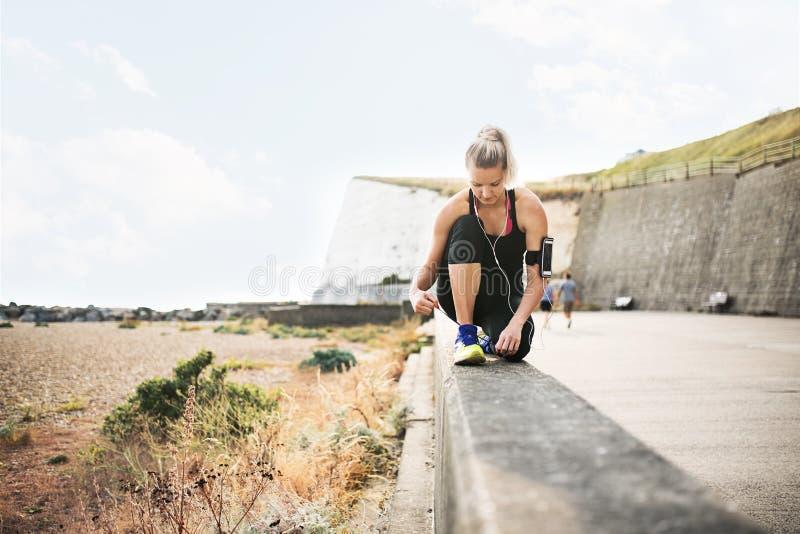 Ung sportig kvinnalöpare med hörlurar som binder skosnöre vid stranden arkivbilder