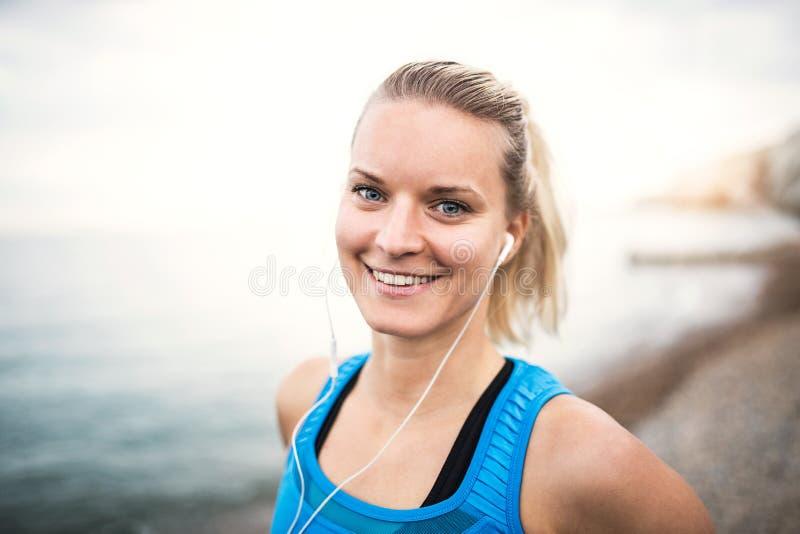 Ung sportig kvinnalöpare med hörlurar som utanför står på stranden arkivbilder