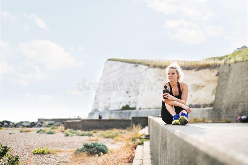 Ung sportig kvinnalöpare med vattenflaskan som utanför sitter på stranden arkivfoto