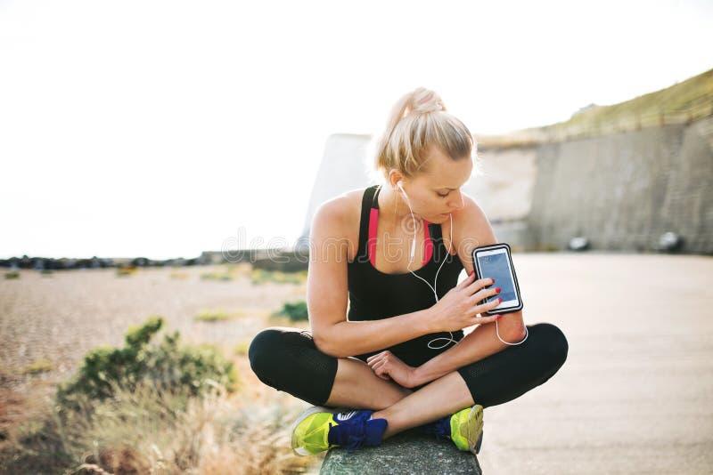 Ung sportig kvinnalöpare som utanför sitter på stranden, genom att använda smartphonen royaltyfri fotografi