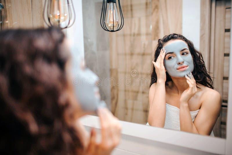 Ung sportig mörker-haired härlig kvinna som gör morgonaftonrutin på spegeln Den trevliga gladlynta modellhandlagframsidan täckte royaltyfri fotografi