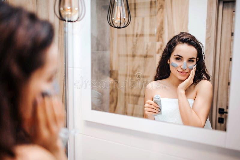 Ung sportig mörker-haired härlig kvinna som gör morgonaftonrutin på spegeln Hon ser i spegel och satte någon maskering arkivfoto