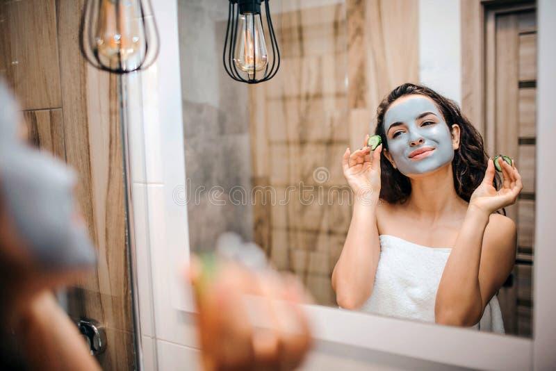 Ung sportig mörker-haired härlig kvinna som gör morgonaftonrutin på spegeln Hon ser och ler Modellhåll två arkivbilder