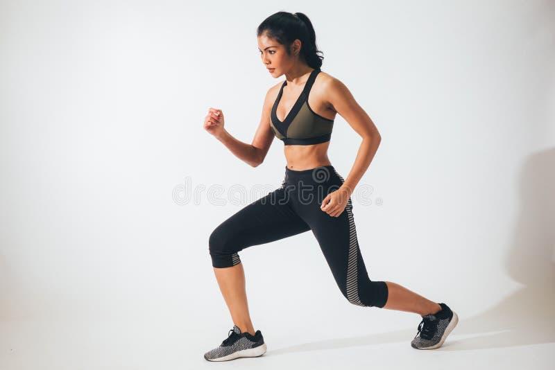 Ung sportig muskulös kvinna som sträcker och värmer upp över vit arkivbild