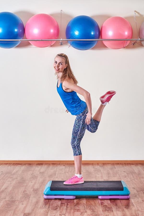 Ung sportive kvinna som övar i idrottshall genom att använda momentplattformen royaltyfri foto