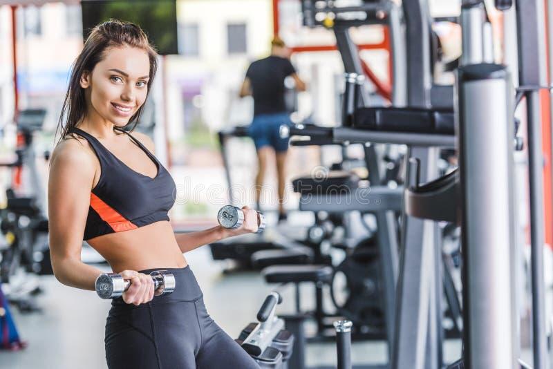 ung sportive kvinna som gör övning med hantlar royaltyfria foton