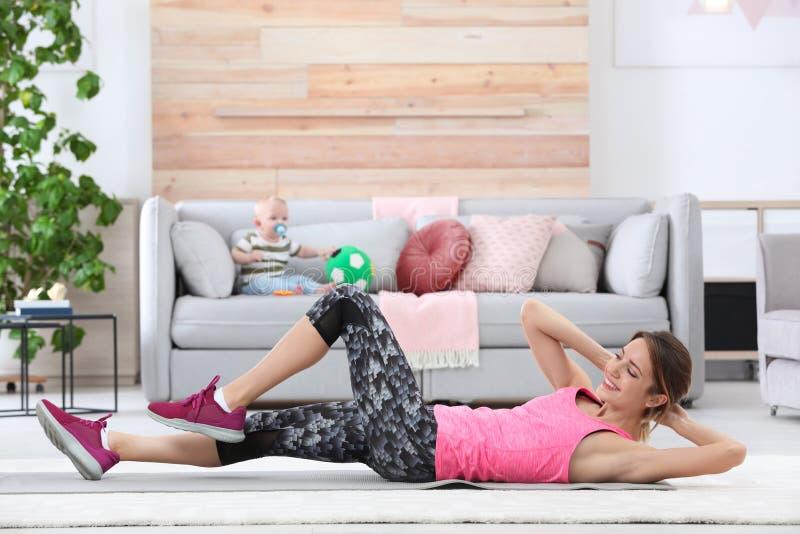 Ung sportive kvinna som gör övning medan hennes son som hemma sitter på soffan royaltyfria foton
