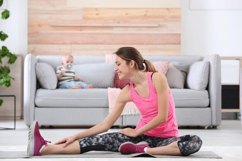 Ung sportive kvinna som gör övning medan hennes son som hemma sitter på soffan royaltyfri foto