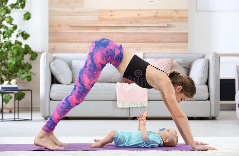 Ung sportive kvinna som hemma gör övning med hennes son royaltyfria bilder