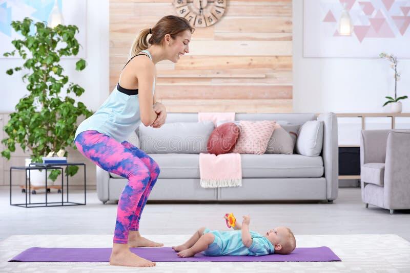 Ung sportive kvinna som hemma gör övning med hennes son, utrymme för text arkivbilder
