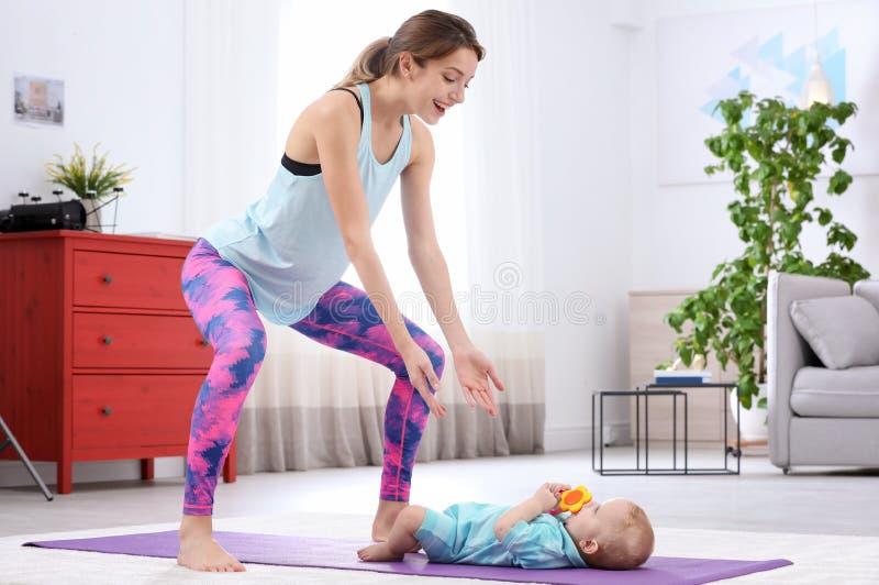 Ung sportive kvinna som hemma gör övning med hennes son, utrymme för text arkivfoton