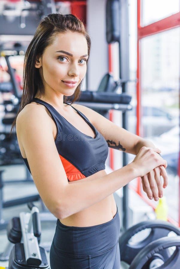 ung sportive kvinna som kontrollerar konditionbogseraren på idrottshallen och att se royaltyfria bilder