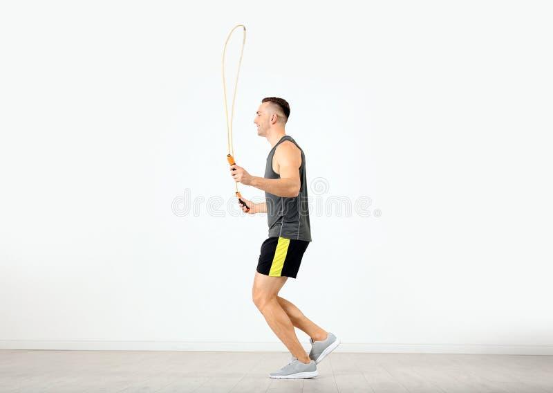 Ung sportive manutbildning med hopprepet i rum arkivfoto