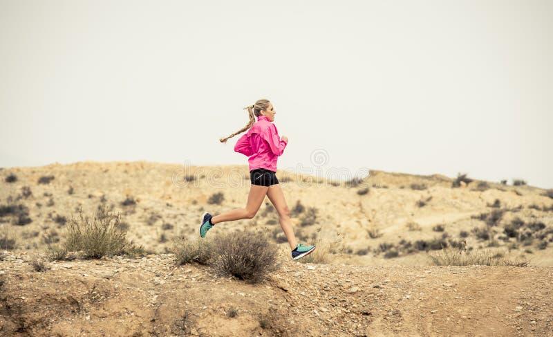 Ung sportkvinna som kör av den smutsiga vägen för vägslinga med torr ökenlandskapbakgrund som hårt utbildar royaltyfri fotografi