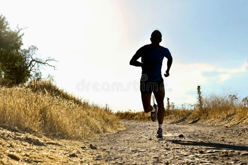 Ung sportman för främre kontur som kör genomkörare för argt land på sommarsolnedgången arkivfoton
