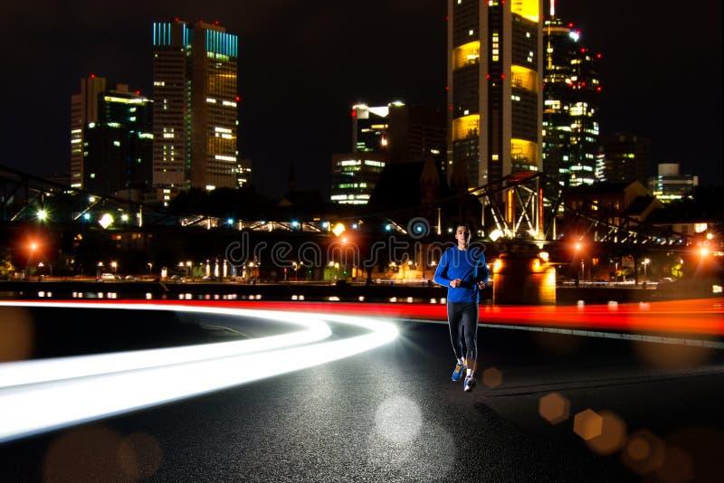Ung sportman som kör på nattvägen med ljusa slingor för bilar Sund livsstil och stads- sportbegrepp arkivbild