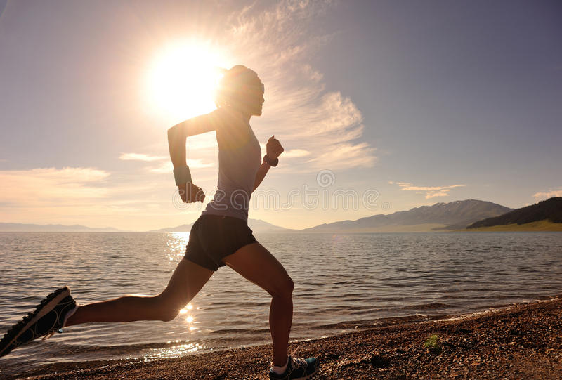 Ung spring för konditionkvinnalöpare på soluppgångsjösidan arkivfoton