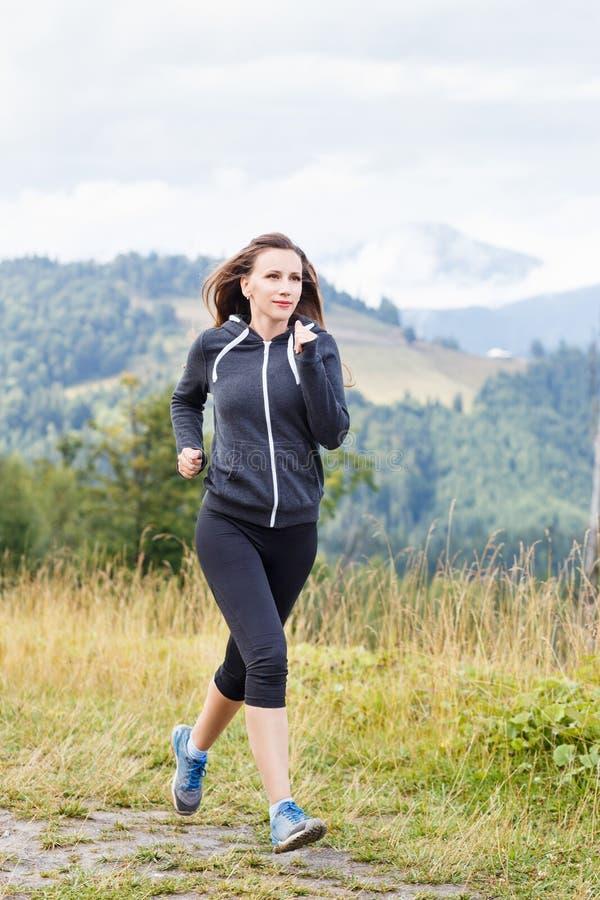 Ung spring för konditionkvinnaslinga i berg fotografering för bildbyråer