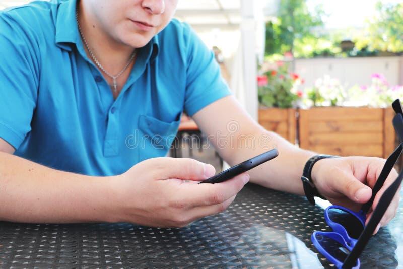 Ung stads- yrkesmässig man som använder den smarta telefonen Hållande mobil smartphone för affärsman genom att använda det smsand royaltyfria foton