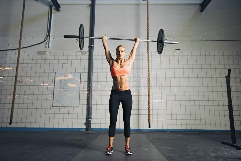 Ung stark kvinna som gör att lyfta för vikt royaltyfri bild