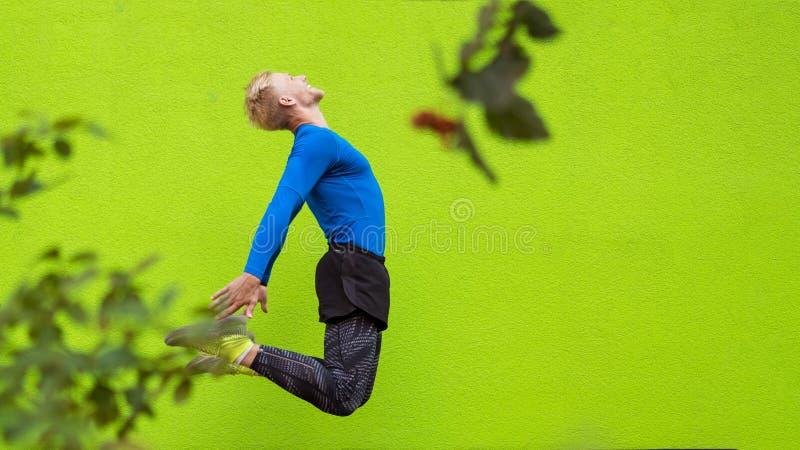 Ung stark man som hoppar på grön bakgrund arkivfoton
