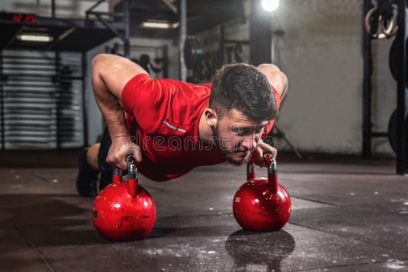 Ung, stark, svettig muskelman med stora muskler som trycker upp på två stora gamla tunga kettlebellar royaltyfri fotografi