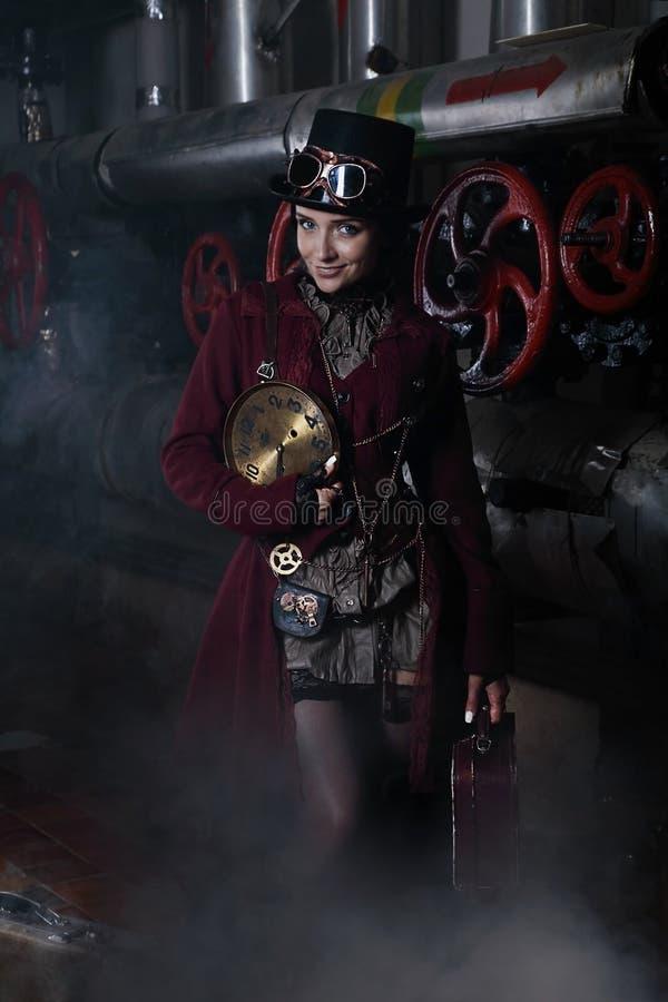 Ung steampunkkvinna med en resväska och en klockaframsida arkivbilder