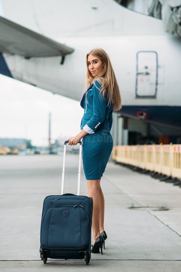 Ung stewardess med resväskan på flygplanparkering arkivfoto