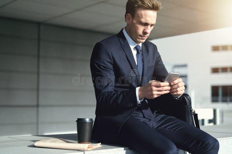 Ung stilfull affärsman, medan genom att använda hans telefon royaltyfri fotografi