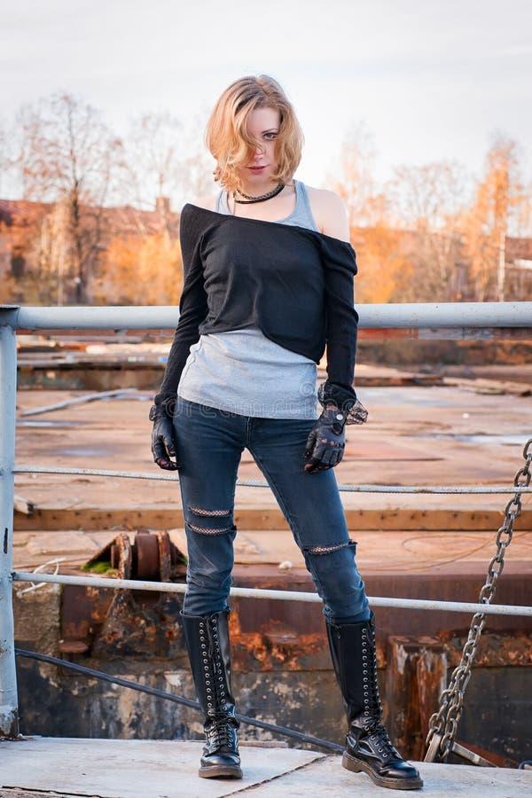 Ung stilfull aggressiv seende kvinna Snöra åt-upp kängor, svart betesmark royaltyfria bilder