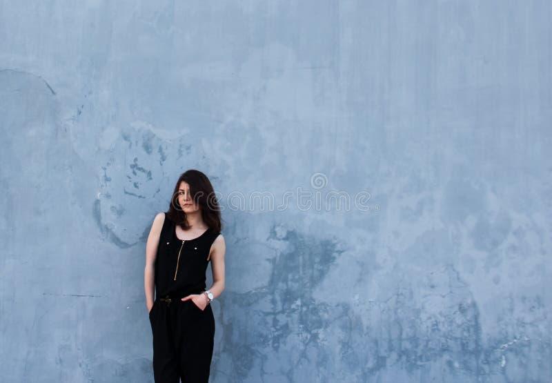 Ung stilfull flicka i en svart dräkt på en blå bakgrund arkivfoton