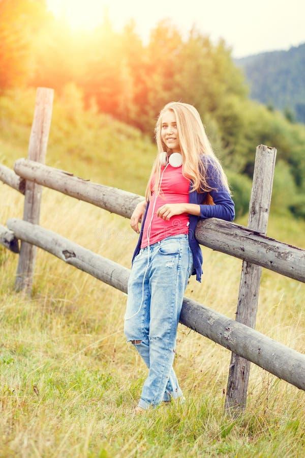 Ung stilfull flicka som står nära staketet i backe fotografering för bildbyråer